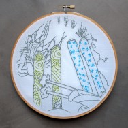 Embroidered illustration of skis and snow for the air Embroidery Club