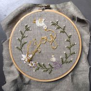 """Embroidery project. The word """"Joy"""" is in the center of the circle, surrounded by green plants and white flowers"""