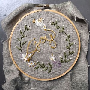 "Embroidery project. The word ""Joy"" is in the center of the circle, surrounded by green plants and white flowers"